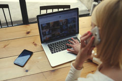 Student blonde is sitting at a laptop in a cafe Stock Photography