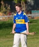 Student in blue and yellow shirt practicing hurling - standing Stock Photo