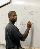 Student at the Board. A handsome african-american student at the board doing trigonometry Royalty Free Stock Images