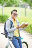 Student with a book. Cheerful Asian student with a book standing outdoors Royalty Free Stock Photos