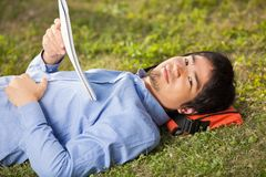 Student With Book Lying On Grass At University Royalty Free Stock Photography