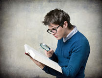 Student with book and magnifying glass. By textured wall Stock Photos