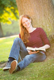 A Student with a Book Smiling at the Camera Royalty Free Stock Photo