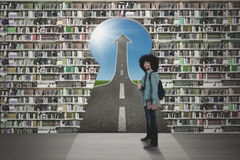 Student with bookcase and keyhole. Male Afro student showing thumb up in front of a bookcase with keyhole and upward arrow Royalty Free Stock Image
