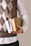 Student with books. The guy is holding a 3 textbooks Royalty Free Stock Image