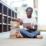 Student With Books And Digital Tablet Sitting In. Full length portrait of young male student with stacked books and digital tablet sitting on floor at library Stock Images