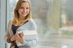 Student with books in front of window Stock Photos