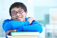 Student with books. Portrait of successful Asian student in eyeglasses looking at camera Royalty Free Stock Images