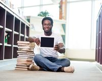Student With Books Showing Digital Tablet In. Full length portrait of confident student with stacked books showing digital tablet while sitting on floor at Stock Images