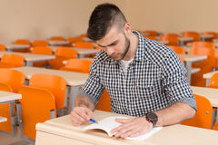 Student With Books Sitting In Classroom. Portrait Of Young Male College Student With Book Sitting In Classroom Alone Royalty Free Stock Photo