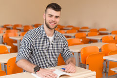 Student With Books Sitting In Classroom. Portrait Of Young Male College Student With Book Sitting In Classroom Alone Royalty Free Stock Image