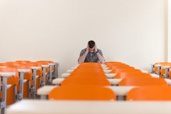 Student With Books Sitting In Classroom. Portrait Of Young Male College Student With Book Sitting In Classroom Alone Stock Images