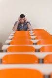 Student With Books Sitting In Classroom. Portrait Of Young Male College Student With Book Sitting In Classroom Alone Royalty Free Stock Photography