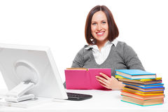 Student with books sitting on workplace. Portrait of smiley student with books sitting on workplace Royalty Free Stock Photography