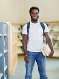 Student With Books Standing in der Buchhandlung Stockfotos