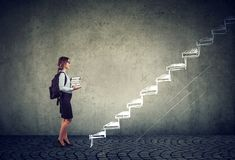 Student with books standing on the stairs of education leading to success. Female student with books standing on the stairs of education leading to success stock images