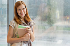 Student with books standing by window Stock Photography
