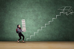 Student with books walks on stairs Royalty Free Stock Photos