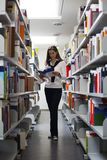 Student between bookshelves reading