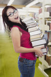 Student borrow many books in library. Attractive female student bring stack of books in the library stock photography