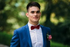 A student with a boutonniere and in a business suit finished his studies. The guy laughs happily walking down the street royalty free stock photography