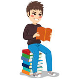 Student Boy Book Stack. Young student boy with casual fashion clothes sitting on stack of books holding notebook education and learning concept Royalty Free Stock Photo
