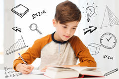 Student boy with book writing to notebook at home. Education, childhood, people, homework and school concept - student boy with book writing to notebook at home Royalty Free Stock Photos