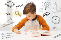 Student boy with book writing to notebook at home Stock Image