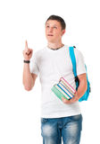 Student boy with books and a backpack. Handsome young man pointing upwards. Portrait of a caucasian guy carrying some books and a backpack, isolated on white Stock Photo