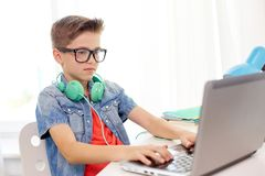 Student boy in glasses typing on laptop at home Stock Photo