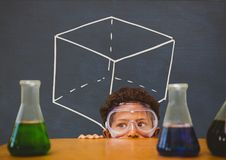 Student boy hiding behind a table against blue blackboard with school and education graphic Stock Photo