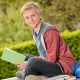 Student boy holding book sitting outside school Royalty Free Stock Image