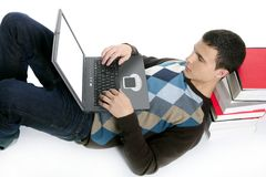 Student boy lying on floor, books and computer Royalty Free Stock Photo