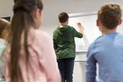 Student boy with marker writing on flip board Royalty Free Stock Images