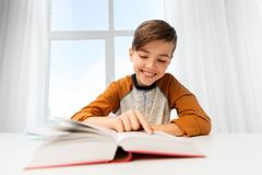 Student boy reading book at home table royalty free stock photo