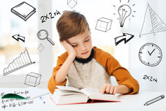 Student boy reading book or textbook at home. Education, childhood, people, homework and school concept - bored student boy reading book or textbook at home over Stock Image