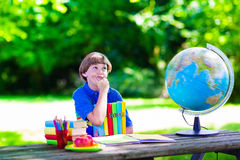 Student boy relaxing in school yard reading books Royalty Free Stock Photo