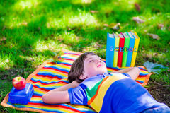 Student boy relaxing in school yard reading books Stock Images