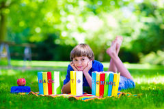 Student boy relaxing in school yard reading books Stock Photos