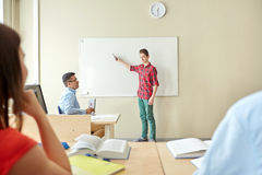 Student boy at school white board and teacher Stock Photos