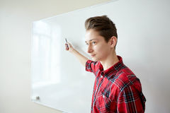 Student boy showing something on blank white board Royalty Free Stock Photo