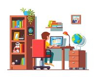 Student boy sitting at desk, doing school homework. Student boy sitting at home office desk, doing school homework, surfing internet on laptop computer. Kids Royalty Free Stock Photography