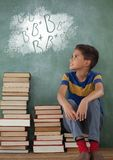 Student boy sitting on a table looking up against green blackboard with school and education graphic. Digital composite of Student boy sitting on a table looking Royalty Free Stock Photos