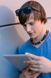 Student boy with tablet leaning against wall Stock Photography