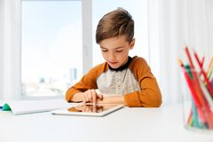 Student boy with tablet pc and notebook at home stock images