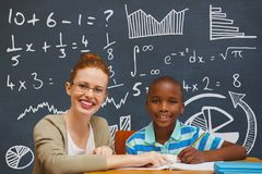 Student boy and teacher at table against blue blackboard with education and school graphics Royalty Free Stock Photos