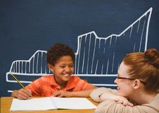 Student boy and teacher at table against blue blackboard with school and education graphic Stock Photography