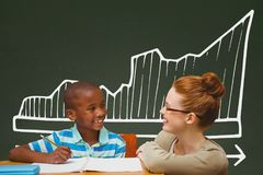Student boy and teacher at table against green blackboard with school and education graphic Royalty Free Stock Photo