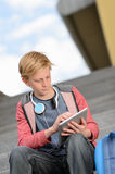 Student boy using tablet sitting on steps Royalty Free Stock Images