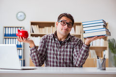 The student breaking piggybank to pay for tuition fees Royalty Free Stock Photos